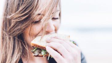une femme mange un sandwich